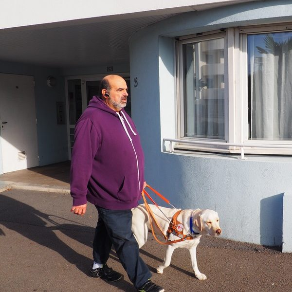 Mr Romano accompagné de son chien guide Jekyll au harnais marchant sur un trottoir