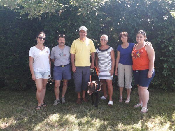 Monsieur Couronne et son chien guide Mambo entouré par la famille d'accueil et les éducatrices