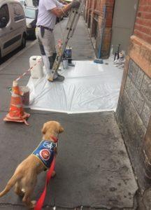 Ohara en ville, sur un trottoir, regarde attentivement des travaux en cours devant un immeuble