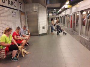 Ohara assise avec sa famille d'accueil sur le quai du métro