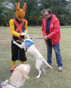 Maïka, élève chien guide et sa famille d'accueil saluent la mascotte du parc Walibi