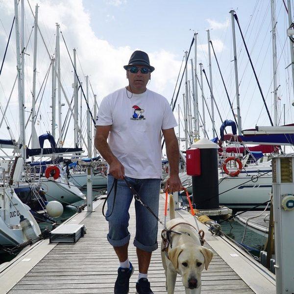 Monsieur Mandico Morales et son chien guide Mao sur un ponton entouré de bâteaux