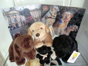Photo des objets à vendre : 3 chiens en peluche : un chocolat, un sable et un noir. Une petite peluche porté-clé en forme de chien de couleur noir et deux puzzles.