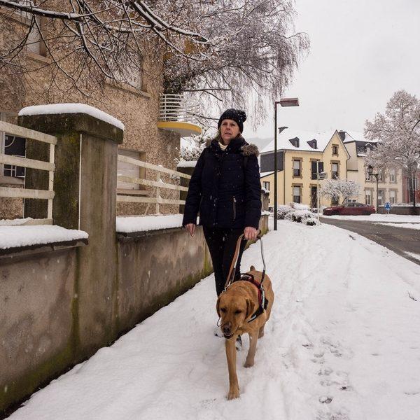 Danielle et son chien guide marchant sur un trottoir enneigé