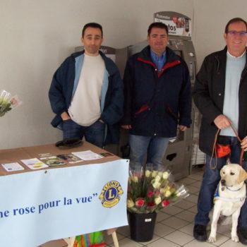 Une famille d'accueil et son élève chien guide sur un stand de vente de rose. Ils sont accompagnés par des bénévoles Lions Club