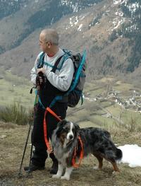 Emir et Bruno son en randonnée sur un chemin de montagne. Au premier plan, on voit un peu de neige dans l'herbe et les sommet aux alentours sont en arrière plan.