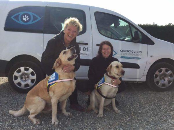 Patricia et Cécile avec deux élèves chiens guides assis deavnt elles. Derrière une voiture de l'Association avec les logos.