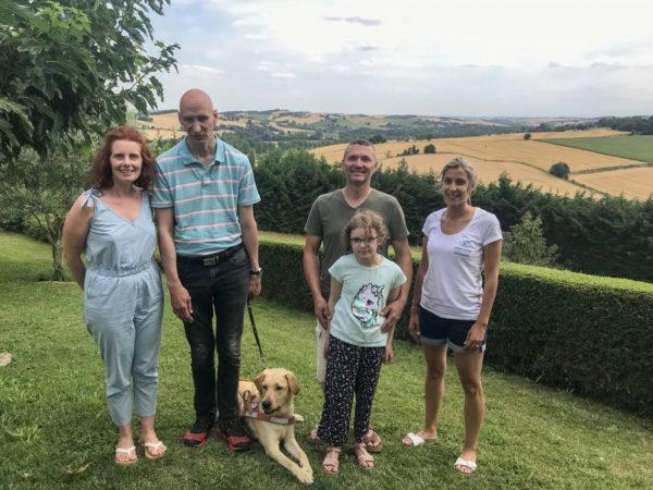 Mr André et Nuts couché à ses pieds entourés par la famille d'accueil et l'éducatrice. La photo est pris en extérieur avec la vue sur les champs