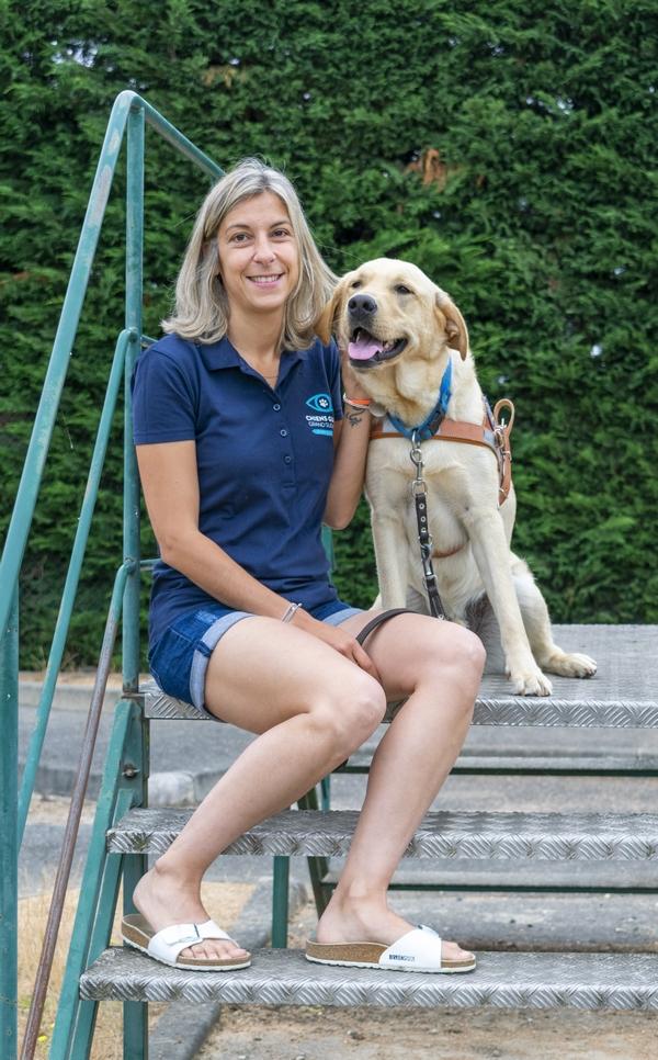 Céline est assise avec Nuts, chien guide en éducation