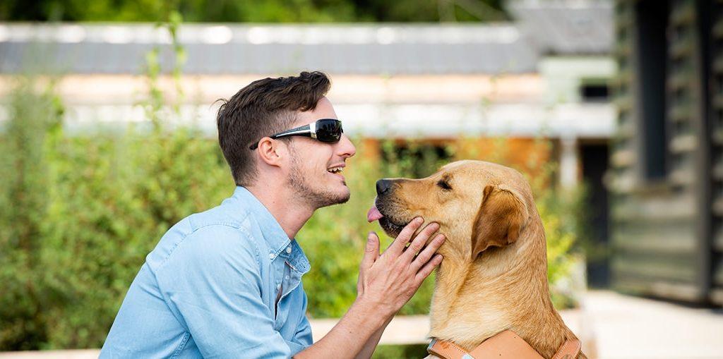 Tom, malvoyant, avec son chien guide. Ils sont face à face