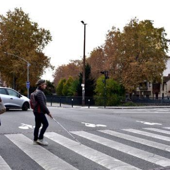Marie, instructrice en locomotion de notre Association, suit une personne déficiente visuelle à un carrefour, lors d'une séance de travail