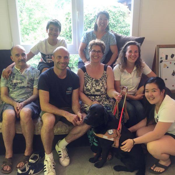 Mme Merzouk et son chien guide/écouteur Mana entourées par la famille d'accueil et les éducateurs