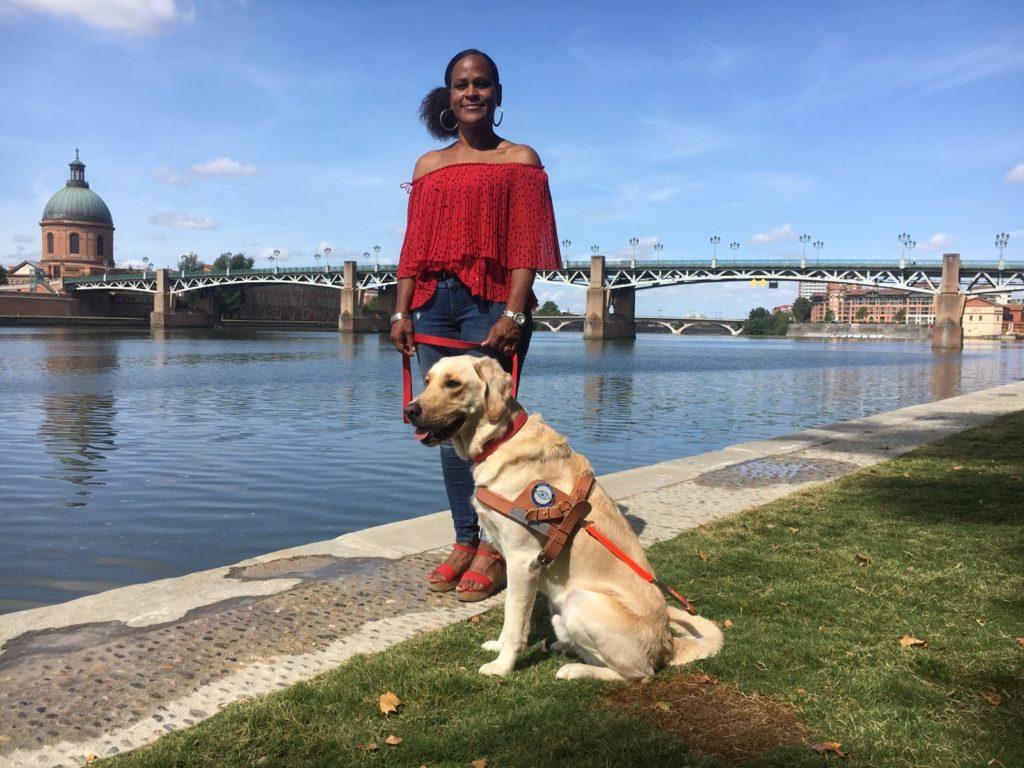 Katherine, personne malvoyante et Milos son chien guide en bord de Garonne