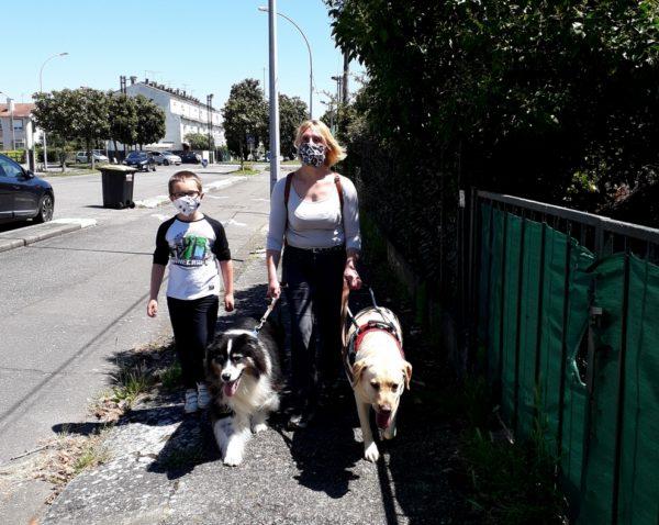Peggy guidée par Nobelle, son chien guide, et accompagnée de Guess, chien à la retraite. Elle marche sur le trottoir avec son jeune fils. Ils portent tous les deux un masque.