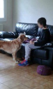 Raphaël assis sur le canapé. Ohara est devant lui, elle le regarde