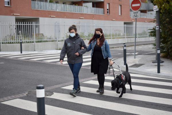 Notre instructrice en locomotion aidant une maîtresse déficiente visuelle à traverser une rue en utilisant le guidage par le bras