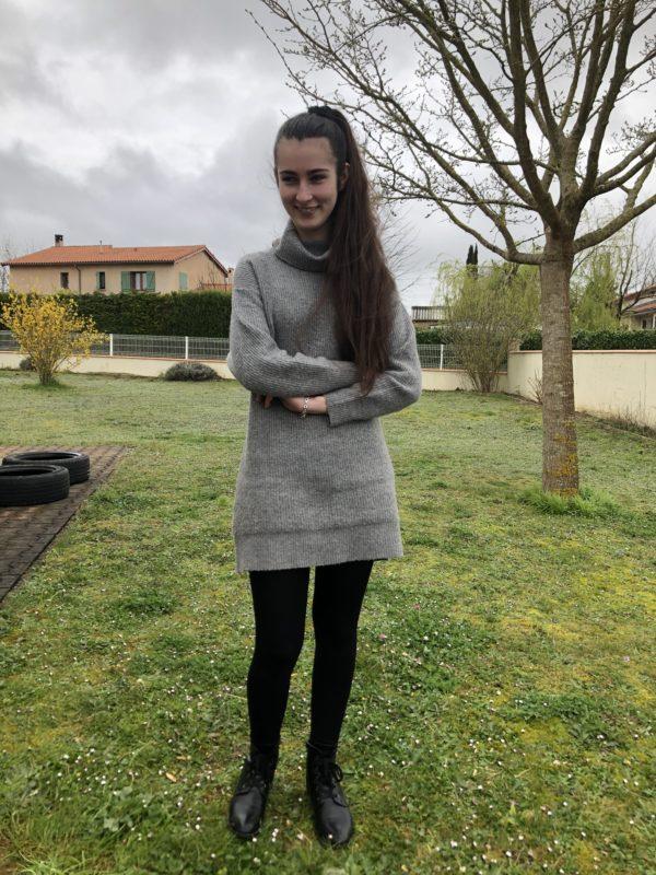 Camille est en demande de chien guide. Sur la photo, elle est debout dans le jardin de sa maison