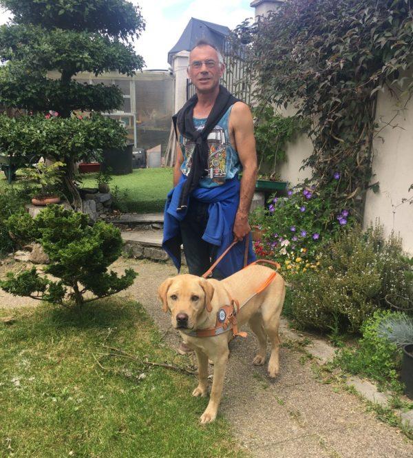 Didier debout dans son jardin avec Pucci portant son harnais de guidage debout à côté de lui