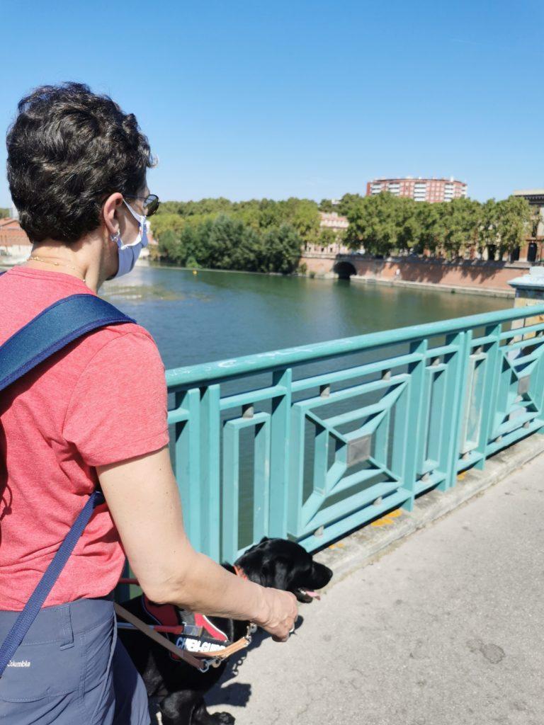 Pascale et Pyrène au harnais marchant sur un pont enjambant la Garonne