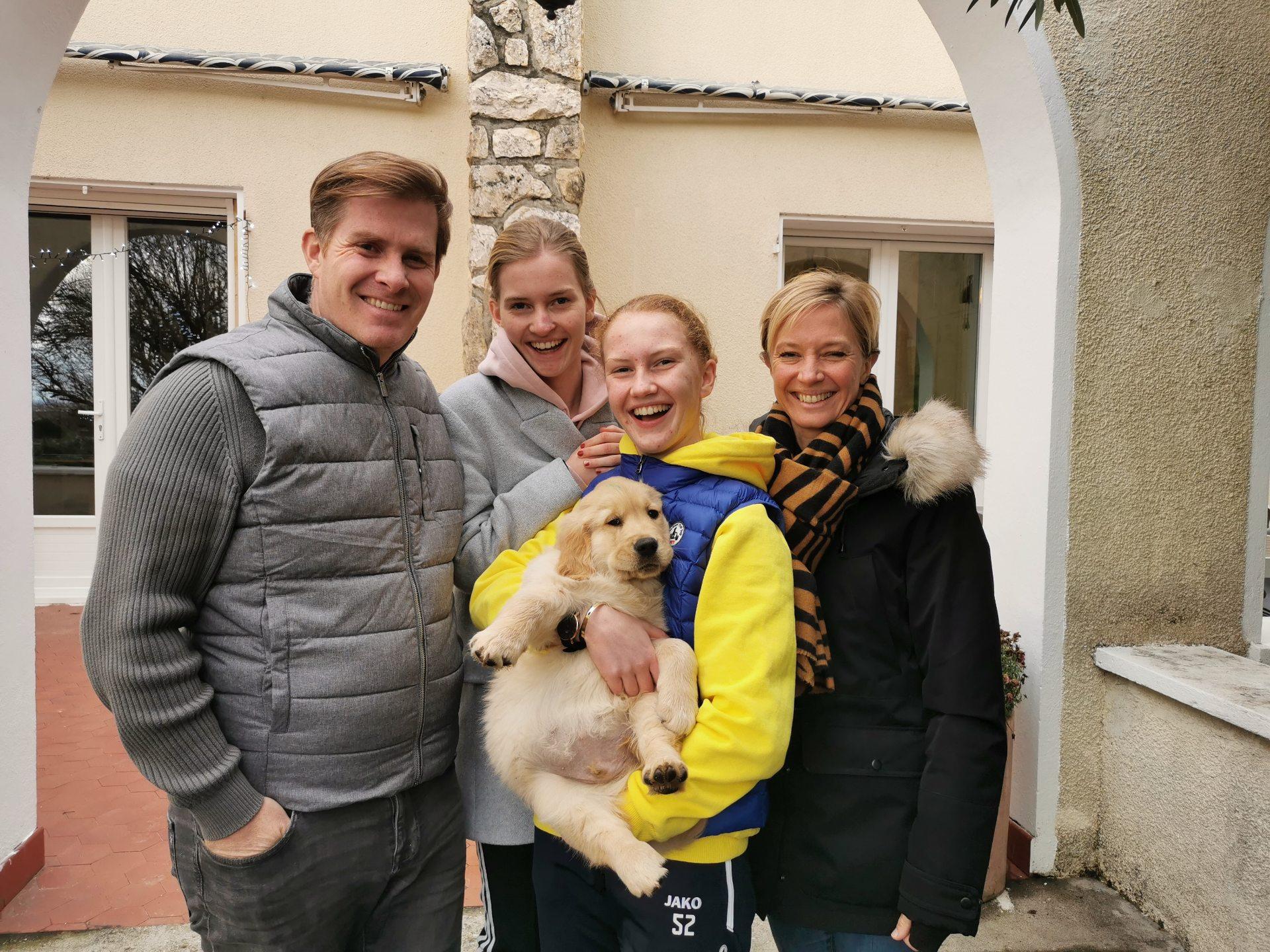 Une famille d'accueil tenant un chiot dans les bras